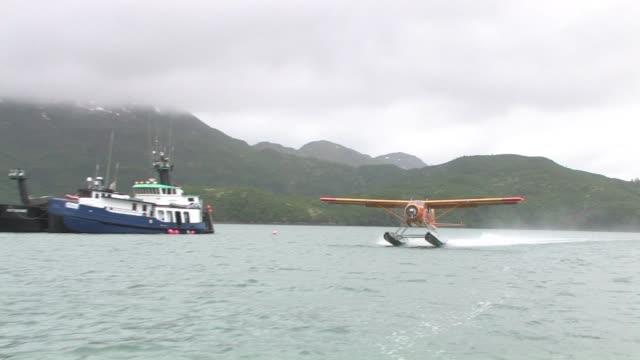 ms, ts, usa, alaska, katmai national park, orange float plane taking off from  bay, green hills in background - 水上飛行機点の映像素材/bロール