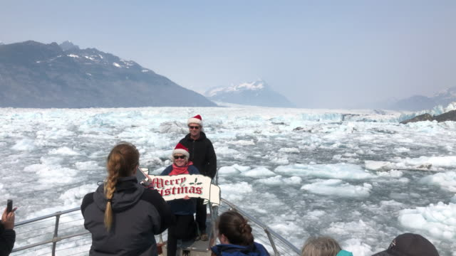 alaska, usa - july 8th, 2019: tourists taking photo with the merry christmas placard with columbia glacier in the background. - positive emotion bildbanksvideor och videomaterial från bakom kulisserna