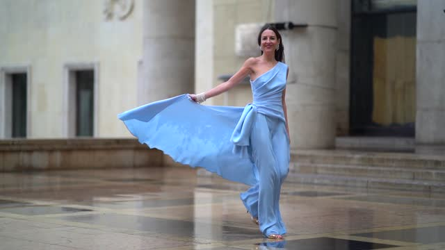 alba garavito torre wears a one-shoulder / off-shoulder flowing top / dress and pale blue flared pants from tony ward, jimmy choo golden sandals,... - grace stock videos & royalty-free footage