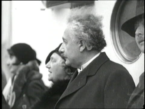 Albert Einstein and his wife Elsa walk down a gangplank as they arrive in New York City