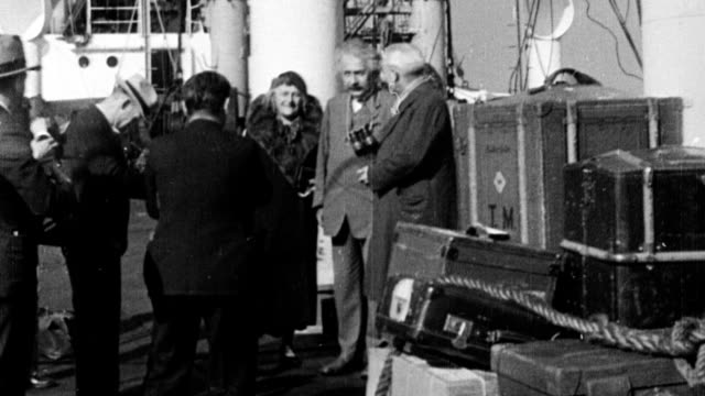 Albert Einstein and wife Elsa Lowenthal pose for photographers upon arrival in US / Einstein walking down ship's gangplank with captain