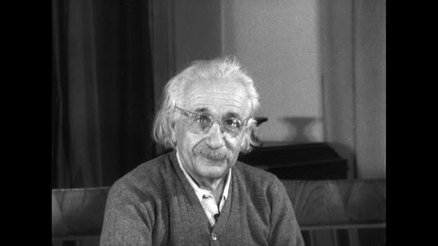 vídeos y material grabado en eventos de stock de albert einstein puts on his glasses before making an address. - e=mc2