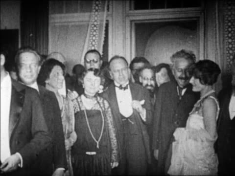 Albert Einstein standing in crowd of people in formalwear after winning Nobel Prize