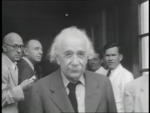 Albert Einstein stands with other officials during a break in a meeting