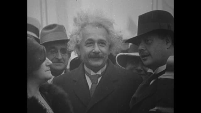 Albert Einstein with his wife Elsa on board a ship with a bunch of people behind him Einstein smiles and speaks / Note exact month/day not known