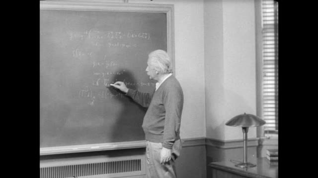 vídeos de stock, filmes e b-roll de / albert einstein writing an equation on blackboard then going to sit down behind his desk albert einstein in his office at princeton university on... - albert einstein