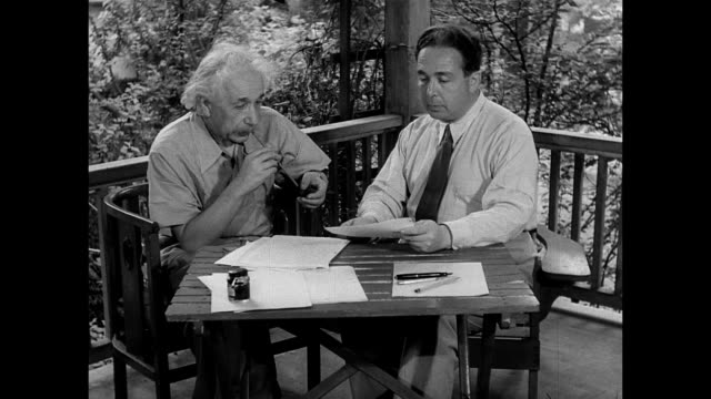 vídeos de stock, filmes e b-roll de albert einstein's home in princeton new jersey theoretical physicist albert einstein w/ physicist dr leo szilard sitting table on porch w/ paperwork... - albert einstein