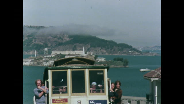 vídeos de stock e filmes b-roll de alcatraz island in distance with trolley bus in foreground - 1970 1979