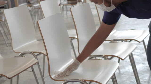 vídeos de stock e filmes b-roll de alcohol spray and wipe a group of chairs - limpar