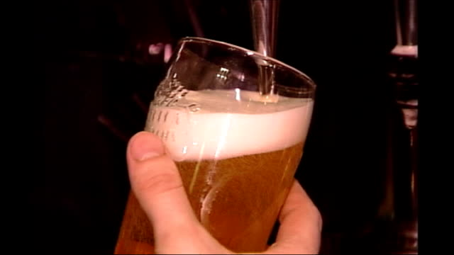 vídeos de stock e filmes b-roll de number of people dying from alcohol related disease rises young men chatting and drinking in bar bartender's hand filling beer glass from tap don... - enchendo