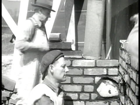 stockvideo's en b-roll-footage met construction alden terrace homes under construction bricklayers working on exterior wall carpenter hammering on frame ext modest twostory northern us... - 1946