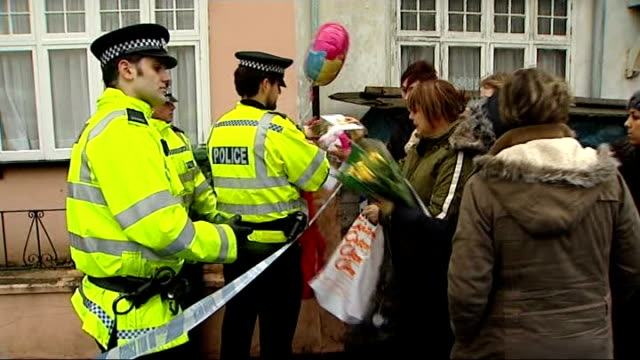 stockvideo's en b-roll-footage met mother dies england hampshire aldershot ext people handing floral tributes soft toys and balloon to police officers outside house where shooting... - aldershot
