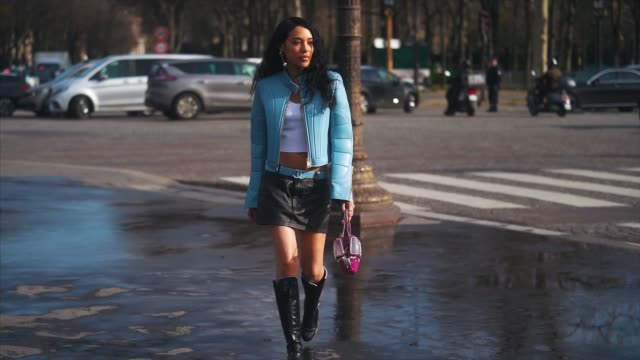 aleali may wears a blue padded jacket, a blue chanel belt, a white cropped top, black leather mini skirt, a pink chanel bag, chanel black leather... - ストリートスナップ点の映像素材/bロール