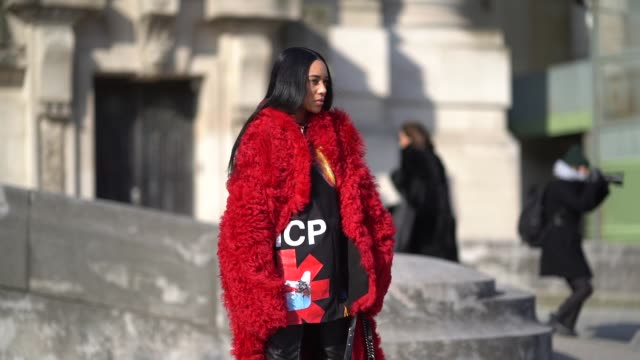 Aleali May wears a Chanel Boy bag a red fluffy faux fur coat black leather boots a flower print dress during Paris Fashion Week Womenswear...