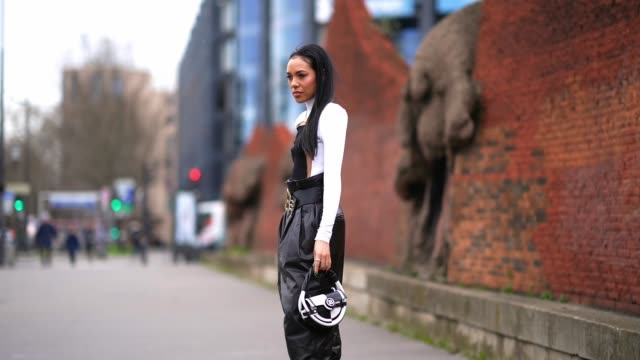 aleali may wears a golden necklace a black and white top a balmain spiked large belt with golden buckle black large puff pants a black and white... - boot stock videos & royalty-free footage