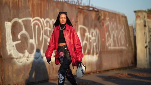 aleali may wears sunglasses a black cropped top a red oversized leather jacket black leather pants with printed joker skull black leather boots a... - boot stock videos & royalty-free footage