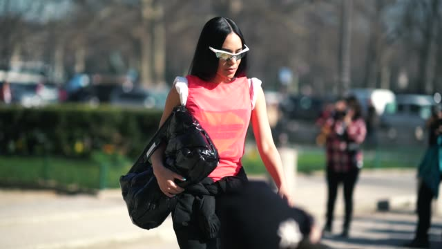 aleali may wears sunglasses, a sleeveless orange top, a black shiny puffer bag, black pants, outside maison margiela, during paris fashion week... - sleeveless top stock videos & royalty-free footage
