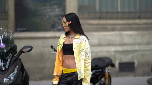 stockvideo's en b-roll-footage met aleali may wears sunglasses a yellow jacket a yellow chanel belt black bras a black leather pants with leather studded straps sneakers outside... - modeweek