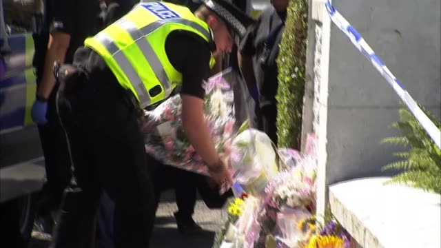 Teenage boy arrested UK Scotland Isle of Bute Police officers by floral tributes and makeshift memorial SCOTLAND Firth of Clyde Isle of Bute EXT...