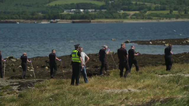 Teenage boy charged SCOTLAND Isle of Bute EXT Various of police officers searching coastline for clues to the murder of Alesha MacPhail