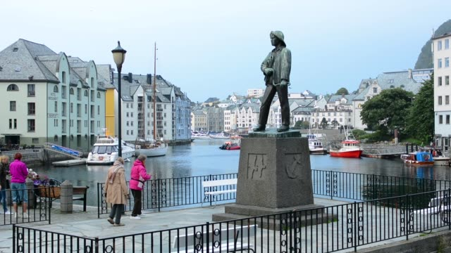 alesund norway cruise hurtigruten downtown near pier sailor's statue with passengers enjoying the scewnic water homes in city - norvegia video stock e b–roll