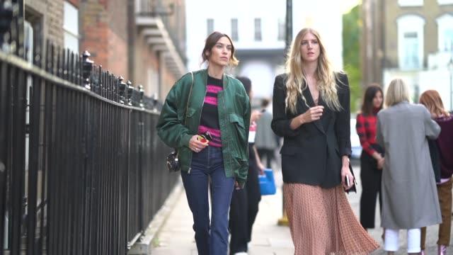 Alexa Chung wears a green bomber jacket blue denim flared pants during London Fashion Week September 2018 on September 16 2018 in London England