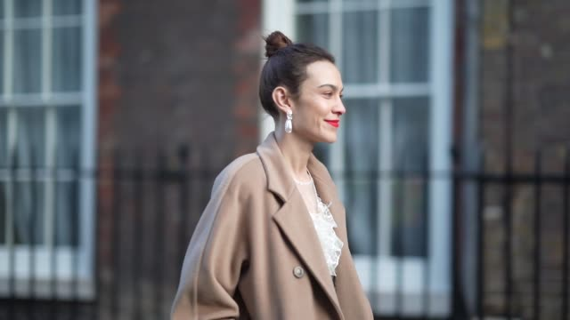 stockvideo's en b-roll-footage met alexa chung wears earrings a pale brown / beige long wool coat a white lace mesh dress black bejeweled shoes during london fashion week fall winter... - jurk