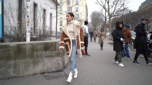 alexandra guerain wears a long aviator jacket, a white top, blue jeans, white shoes, outside acne, during paris fashion week - menswear f/w... - 長さ点の映像素材/bロール