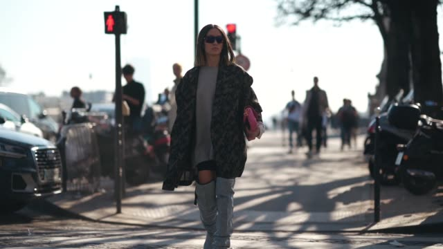 alexandra guerain wears a military camouflage print coat, sunglasses, a pink bag, thigh high boots, a gray top, outside unravel project, during paris... - thigh stock videos & royalty-free footage