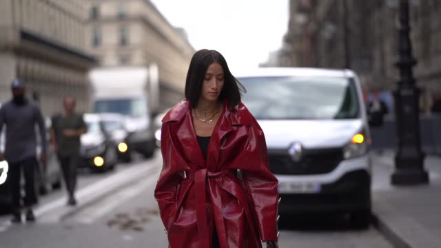 vídeos de stock e filmes b-roll de alexandra guerain wears necklaces a black top a shiny red vinyl trench coat with buttons at the cuffs transparent vinyl heeled slingback pumps a... - sapato aberto atrás