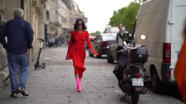 alexandra guerain wears sunglasses necklaces a black bag a long sleeves gathered asymmetric red dress neonpink midcalf sockboots outside unravel... - neon stock videos & royalty-free footage