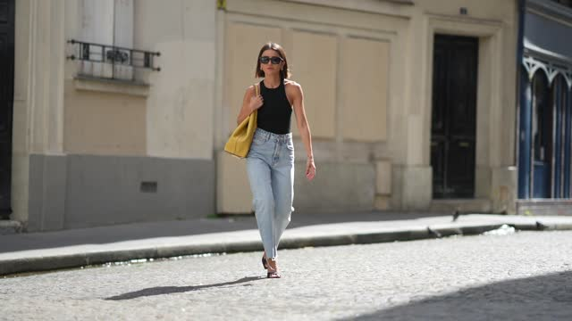 alexandra pereira wears black sunglasses, gold earrings, a black ribbed halter-neck cropped t-shirt, blue faded denim high waist ripped flared jeans... - brown hair stock videos & royalty-free footage