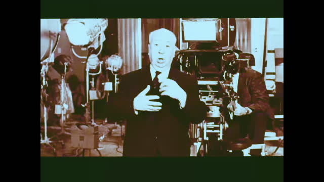 alfred hitchcock stands up from the directors chair, surrounded by film crew and equipment, talking to the camera and explains to the audience the... - film set stock videos & royalty-free footage