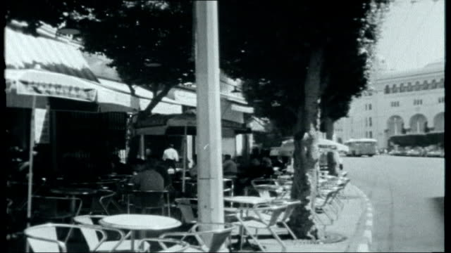 ben bella overthrown group of men sat at table outside cafe drinking coffee and reading newspapers / other people sat at cafe tables under umbrellas... - turban stock videos & royalty-free footage