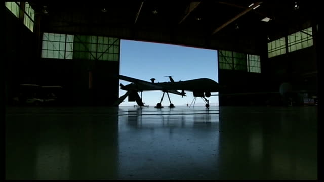 fears for safety of hostages after troops storm gas facility tx usa arizona int silhouette of drone as doors to hangar open drone in flight - アルジェリア人質事件点の映像素材/bロール