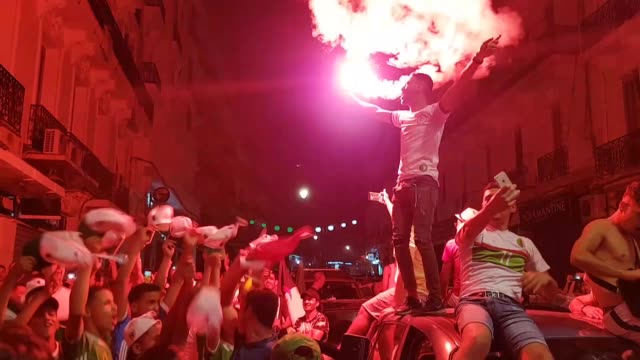 Algeria's supporters wave the Algerian national flag as they celebrate on the streets of Algiers after Algeria won 10 the 2019 Africa Cup of Nations...
