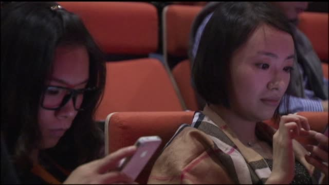 Alibaba employees using mobile devices in Hong Kong China on November 19 Closeups of cell phone usage Wide shots of users on phones tablets and...