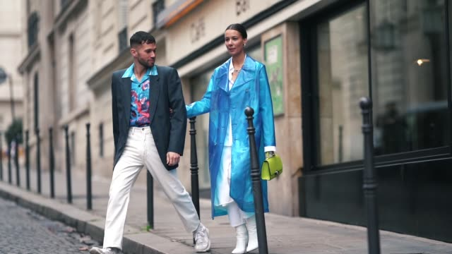 alice barbier wears a blue clear trenchc oat, white pants, white shoes, a neon yellow bag ; jean-sebastien rocques wears a blazer jacket, a floral... - jacket stock videos & royalty-free footage