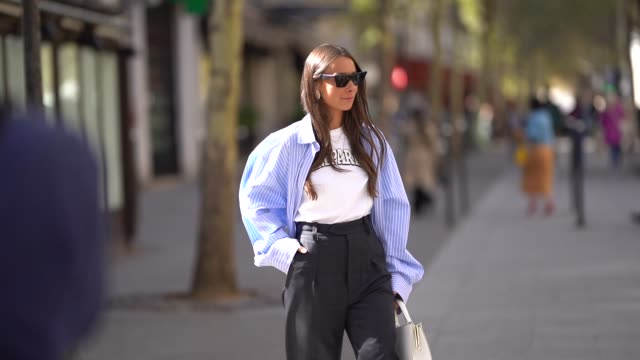 vídeos y material grabado en eventos de stock de alice barbier wears a blue shirt, a white t-shirt, black flare pants, white shoes, outside altuzarra, during paris fashion week womenswear... - camiseta
