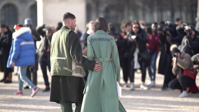alice barbier wears a green trench coat, a green cropped top, flare pants ; jean-sebastien rocques wears a khaki long coat, green flare pants,... - トレンチコート点の映像素材/bロール