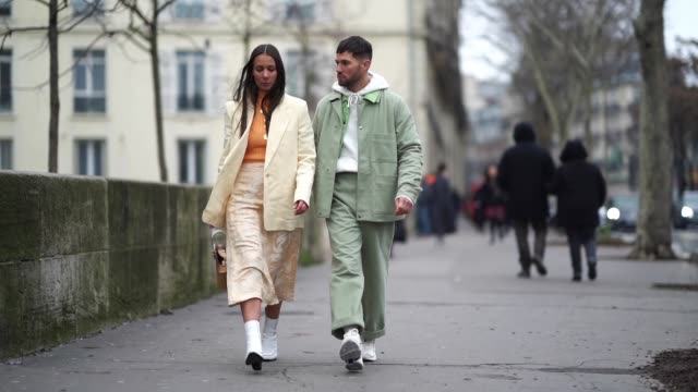 Alice Barbier wears a white blazer jacket cropped pants white boots a brown bag JeanSebastien Rocques wears a green jacket a white hoodie sweater...