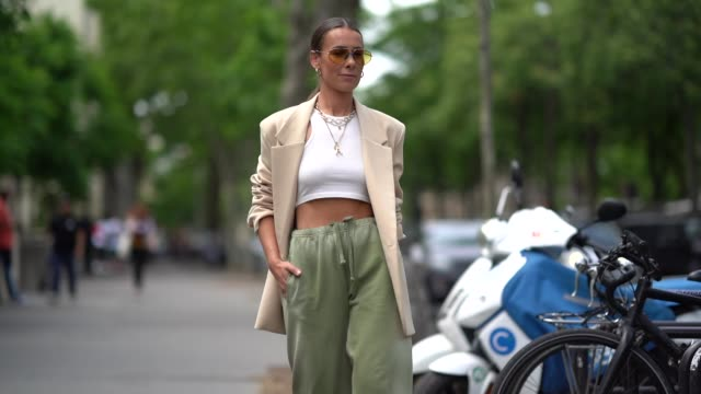 vídeos de stock e filmes b-roll de alice barbier wears earrings sunglasses necklaces a white crop top a beige jacket pistachio green pants with a sliding belt and elastic leg hems a... - sandália