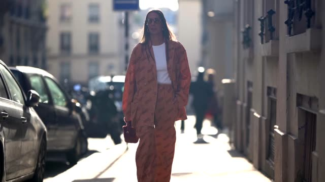 vídeos de stock e filmes b-roll de alice barbier wears sunglasses a white tshirt a brown pattern salmoncolored suit with elastic waist and wide leg pants a rustcolored hand bag white... - calças