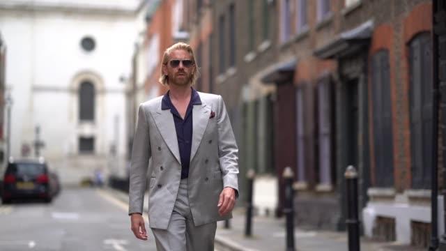Alistair Guy wears a gray blazer jacket a dark blue shirt flare pants shoes during London Fashion Week Men's June 2019 on June 09 2019 in London...