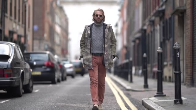 alistair guy wears a gray wool turtleneck pullover, a khaki jacket, orange pants, sunglasses, suede shoes, during london fashion week men's january... - gray jacket stock videos & royalty-free footage