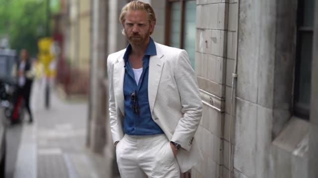 Alistair Guy wears sunglasses a blue shirt a white blazer jacket white suit pants blue shoes during London Fashion Week Men's June 2018 on June 10...