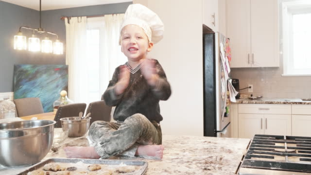 all credit goes to me! - young boy cheering on the kitchen counter wearing chef's hat - baking stock videos & royalty-free footage
