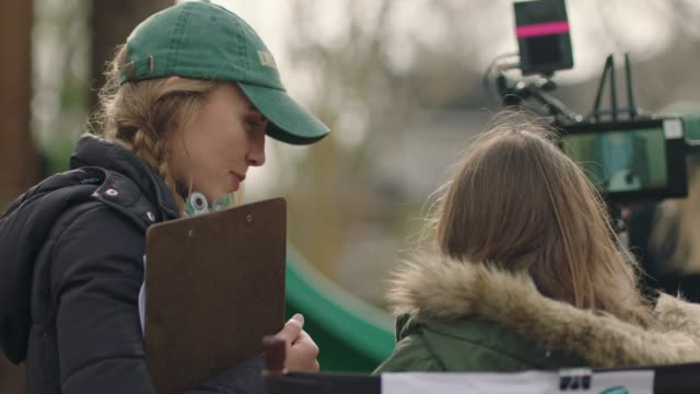 vidéos et rushes de all female filmmakers works on outdoor set as a young child director watches the action on a wireless monitor. - bloc note