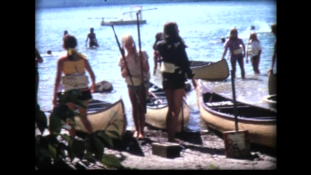 1968 all girls launching canoes and paddling away