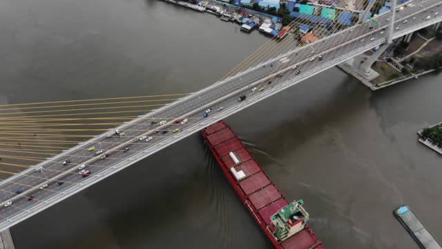 all large cargo vessels that are passing under the suspension bridge with car traffic - southeast asia stock videos & royalty-free footage